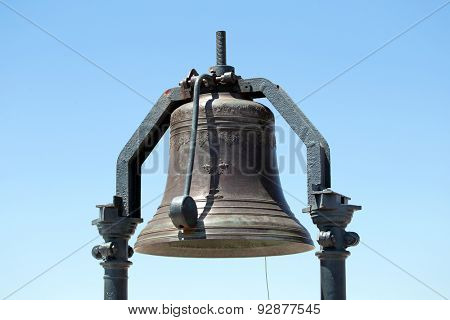 Antique bell against a blue sky