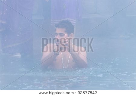 Indian Man Take Holy Bath In The River Ganges At Cold Foggy Winter Morning. Varanasi