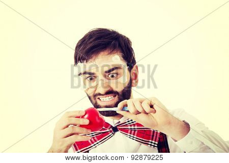 Determined man wearing suspenders cutting heart model with scalpel..