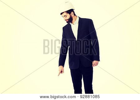 Smiling businessman with hard hat pointing down.