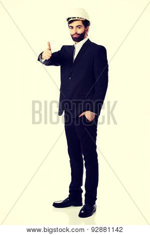 Smiling businessman with hard hat showing ok sign.