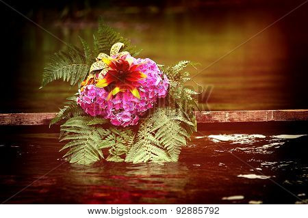 Flowers lie on the old board with water