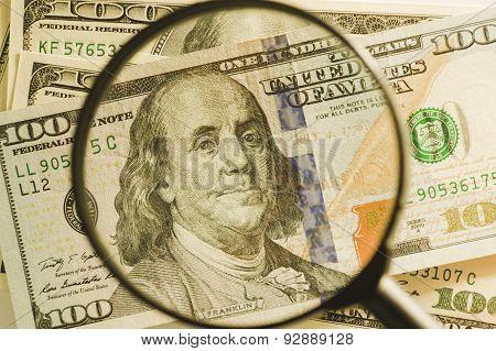 One hundred dollar bills through magnifying glass
