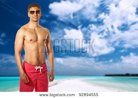 Man on beach with sandspit at Maldives.