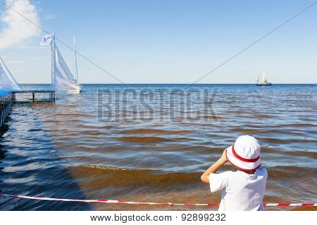 The Child Looks At The Sea With Binoculars