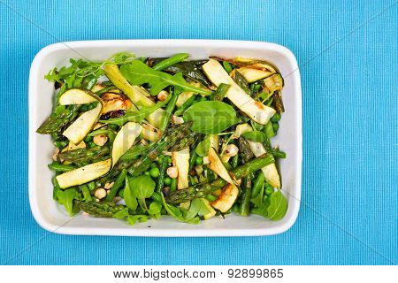 Asparagus, Courgette And Hazelnut Salad In A Rectangular Dish From Above On A Blue Napkin