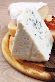 pic of cheese platter  - various types of cheese on wooden platter over wooden table - JPG
