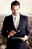 foto of concentration  - Concentrated businessman using magnifying glass against new york - JPG
