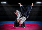 stock photo of judo  - Fight between two martial arts fighters at sports hall - JPG