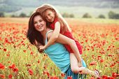 picture of preteens  - Mother and her 7 years old preteen child playing in spring poppy field in soft sunlight - JPG