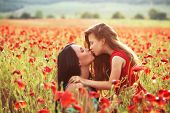 picture of preteen  - Mother and her 7 years old preteen child playing in spring poppy field in soft sunlight - JPG