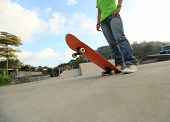 picture of skateboard  - closeup of young skateboarder legs and skateboard at  skateparks - JPG