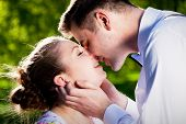 stock photo of fiance  - Young romantic couple kissing with love in summer park - JPG