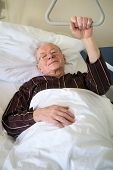 stock photo of ward  - Frail senior man lying in a hospital bed on a ward recuperating from an illness or operation lying resting with his glasses on and eyes closed and a quiet smile - JPG