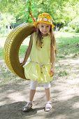 image of tire swing  - Girl in yellow dress standing near tire swing - JPG