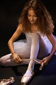 picture of ballet shoes  - Pretty young ballet student tying lace on ballet shoe - JPG