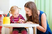 stock photo of babysitter  - Young mother and her little daughter drawing together - JPG