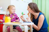 stock photo of babysitter  - Young mother and her toddler girl playing together with finger toys - JPG