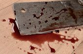 stock photo of slaughterhouse  - Old rusty meat cleaver with blood on a wooden floor - JPG