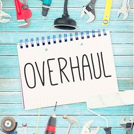 stock photo of overhauling  - The word overhaul against tools and notepad on wooden background - JPG