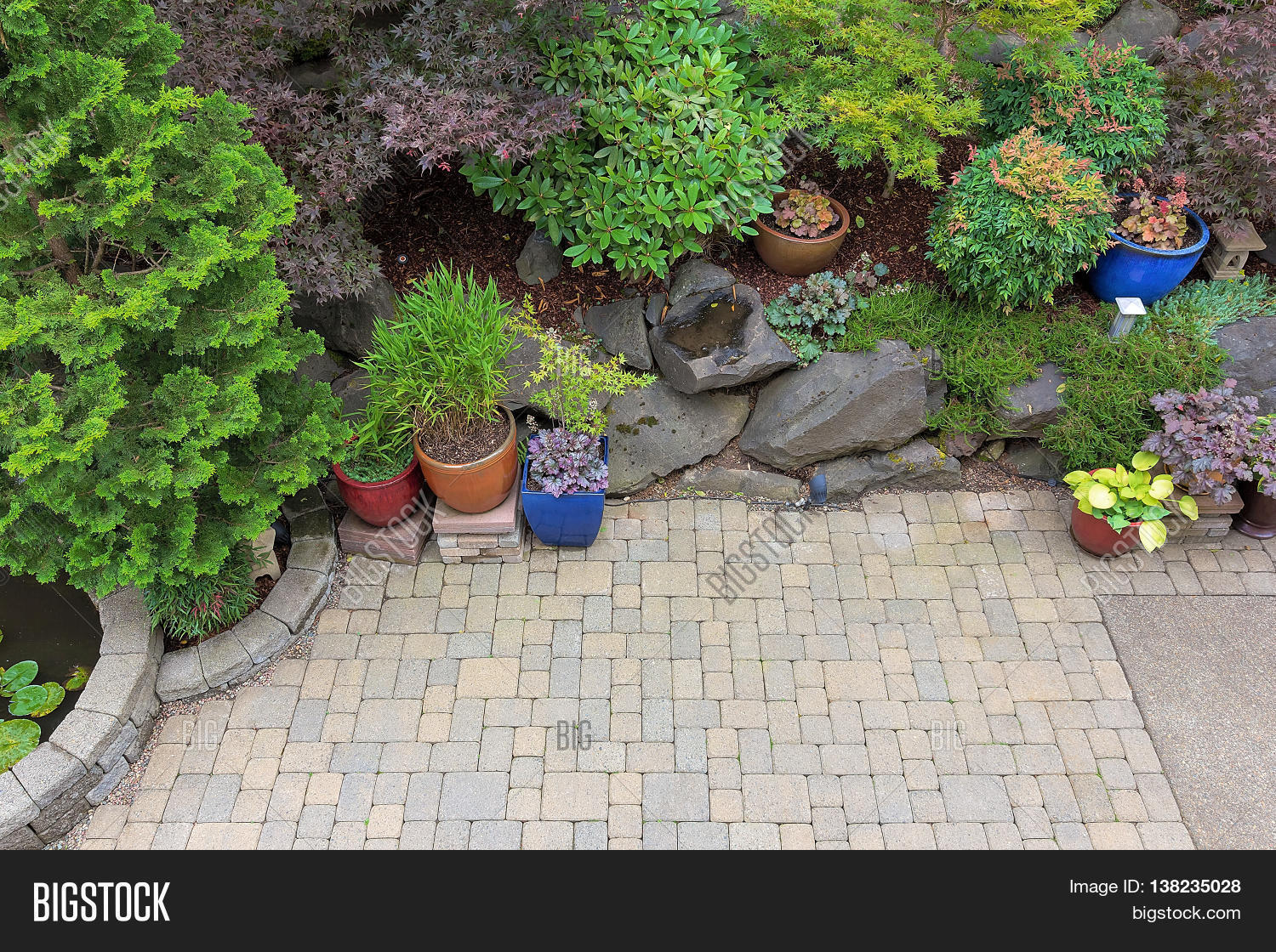 Backyard Garden Landscaping With Paver Bricks Patio Hardscape Trees Potted  Plants Shrubs Pond Rocks And Decor