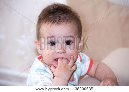 Baby boy plays with fingers in mouth and happy facial expression. Portrait of a crawling baby smiling. Teething infant playing. Newborn child at home. child scratching his teeth.