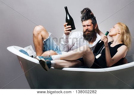Young Couple In Bath With Wine Bottles