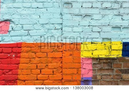 the old textured surface of a brick wall with multicolored spots for vintage background or for retro wallpaper