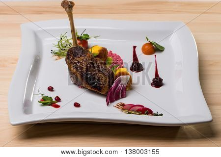 Confit duck or goose leg crisp delicious served with garnish colorful vegetables and blackberry sauce on wooden background