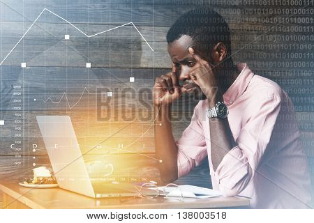 Young African Marketing Expert In Pink Shirt Working Late Hours Using Laptop, Looking At The Screen