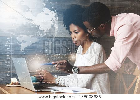 Worldwide Connection Interface. African Executive Officer In Glasses Holding A Pen Pointing At The L