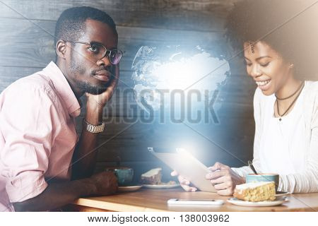 Internet Addicted Young Dark Skinned Woman Sitting With Happy Smile In Front Of Her Angry Boyfriend,