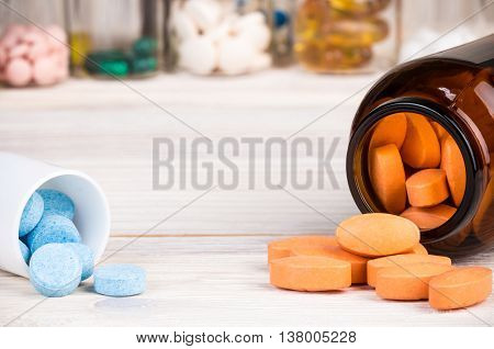 Orange pills in dark brown glass container and blue pills in plastic container with other color pills in background
