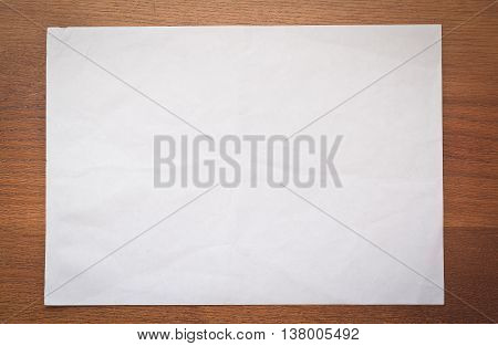 blank sheet of paper on a wooden table