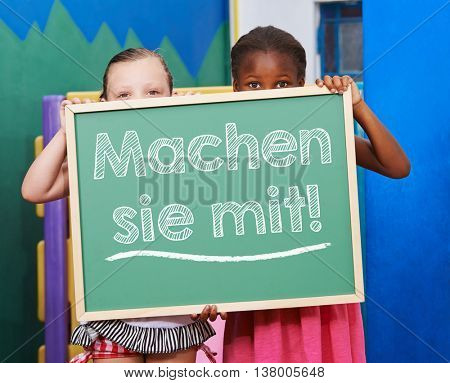 Two children holding a chalkboard with German slogan