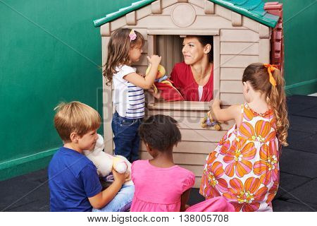 Group of children watching puppet theater play in a kindergarten