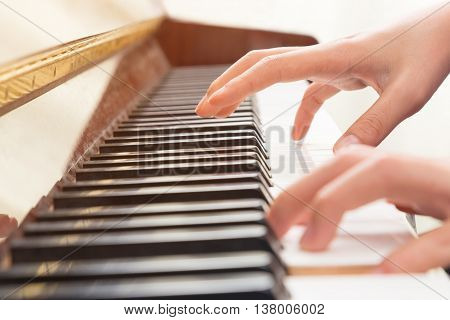 Close up of female hands playing piano with one hand on the keys the other hand floating above and about to hit the keys selective focus on the hand above the keys