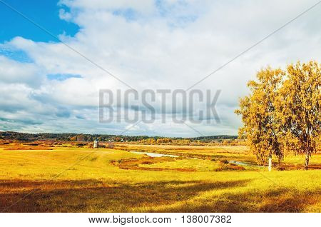 Autumn sunny landscape with autumn colorful view of Soroti river valley in Pushkinskiye Gory Russia - autumn natural landscape of autumn yellowed nature in sunny autumn weather. Soft focus applied
