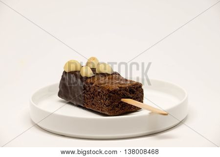 Decorative brownie with stick on the white plate.