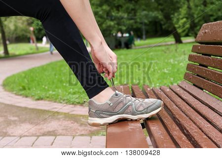 Tying shoelaces on sneakers sports. Close-up. Bench.