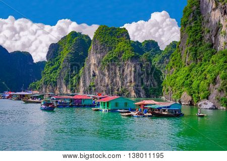 Floating fishing village near rock islands in Halong Bay Vietnam Southeast Asia. UNESCO World Heritage Site.