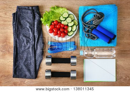 Sport equipment   healthy food   wooden background, top view