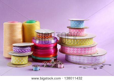 Spools of color ribbons on purple background