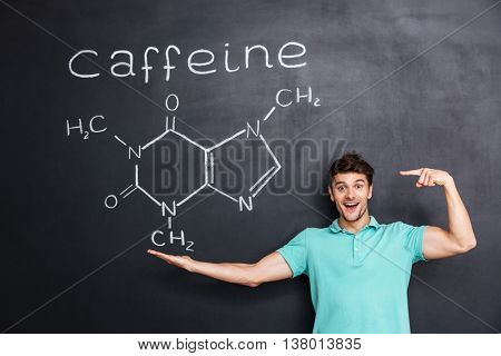 Cheerful young teacher standing and pointing on chemical structure of caffeine molecule drawn on chalkboard background