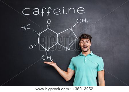 Cheerful young scientist showing chemical structure of caffeine molecule drawn on chalkboard background