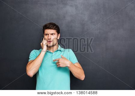 Confused handsome young man standing and talking on cell phone over chalkboard background
