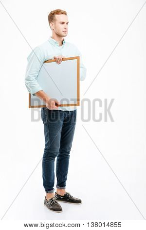 Full length of serious redhead young man standing and holding whiteboard