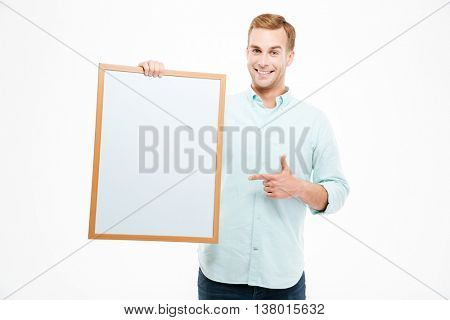 Cheerful young man holding blank white board and pointing on it over white background