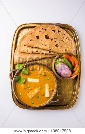 indian food paneer butter masala served with chapati / roti / paratha / fulka / indian bread with green salad