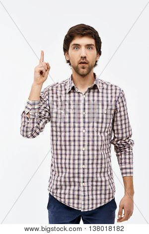 Close-up portrait of handsome thinking young blue-eyed dark-haired man wearing casual plaid shirt and jeans looking at camera, pointing upward. Isolated on white background.